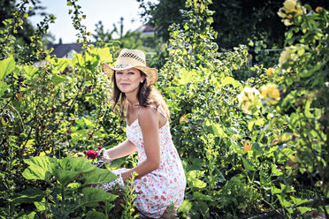 Portrait of smiling woman working in the garden - VTF000440