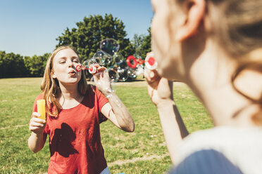 Two teenage girls blowing soap bubbbles in park - AIF000087
