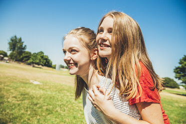 Teenage girl carrying friend piggyback in park - AIF000050