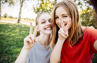 Two playful teenage girls making victory sign - AIF000052