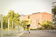 Germany, Stuttgart, smiling man jogging in the city - JUNF000418