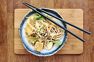 Asian noodle salad with soba noodles, tofu, green onions, yellow zucchini and coriander, garnished with black sesame seeds - HAWF000829