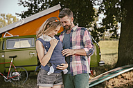 Smiling couple with baby in in front of van in the nature - MFF002007
