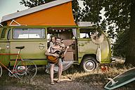 Smiling woman hugging man in van playing guitar - MFF002013