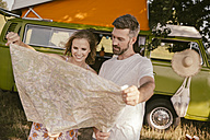 Couple looking at map in front of van in the nature - MF002055