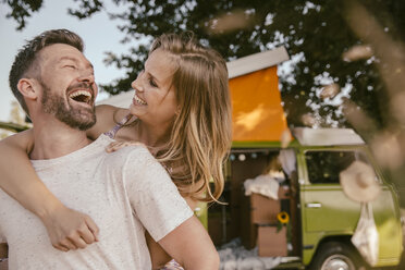 Playful couple in front of van in the nature - MFF002031