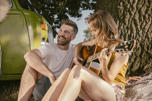 Couple making music at tree beside van - MFF002042