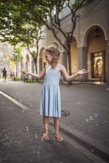 Germany, Berlin, Girl playing with soap bubble in the street - OPF000064