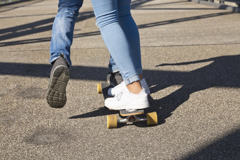 Legs of young couple driving on a skateboard - MEMF000943