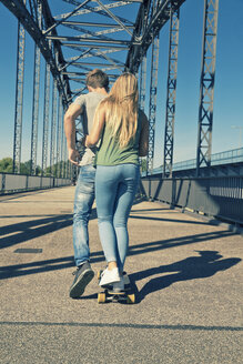 Back view of young couple in love on a skateboard - MEMF000938