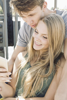 Young couple looking together on smartphone - MEMF000939