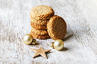 Stack of whole grain cocos cookies and Christmas decoration on wood - EVGF002078