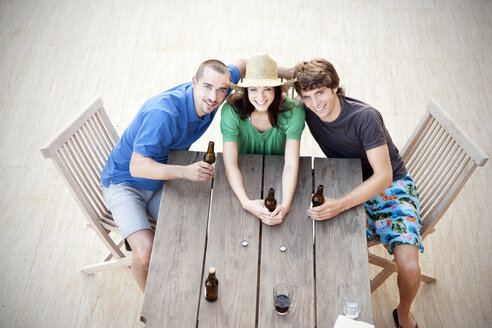 Happy friends sitting at wooden table drinking beer - TOYF001064