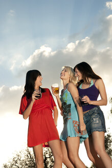 Three happy young women having a party outdoors - TOYF001077