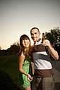 Happy young couple with beer bottle at sunset - TOYF001089