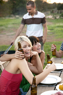 Happy friends embracing at garden table on a barbecue with beer bottles - TOYF001218