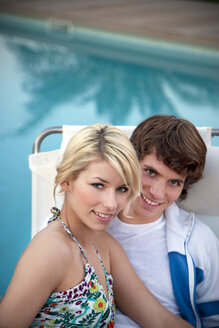 Portrait of smiling couple at the poolside - TOYF001096