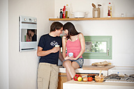 Smiling young couple face to face in the kitchen - TOYF001104
