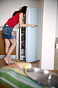 Young woman standing in the kitchen searching something in the fridge - TOYF001107