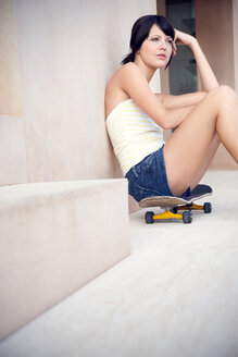 Young woman sitting on her longboard leaning against wall - TOYF001133