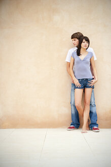 Portrait of young couple leaning against wall - TOYF001141