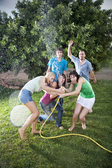 Five friends splashing with water in the garden - TOYF001150