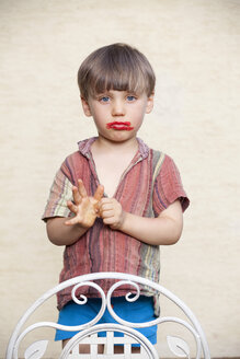 Portrait of litte boy with red lipstick on his face pouting mouth - NDF000548