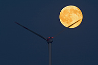 Germany, rise of full moon with wind wheel in the foreground - UMF000793
