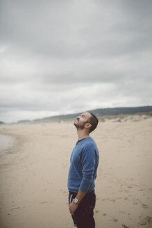 Spain, Ferrol, man standing on the beach looking up - RAEF000336