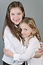 Two little sisters hugging - ECF001818