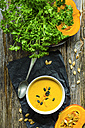 Selfmade pumpkin soup with pumpkin seeds and parsley on a wooden table - ODF001219