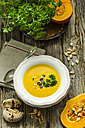 Selfmade pumpkin soup with pumpkin seeds, parsley and a bun of olives and tomatoes on a wooden table - ODF001222