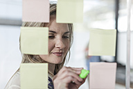 Woman in office writing on sticky notes - ZEF007470