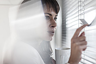 Woman in office looking through blinds - ZEF007421