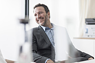 Smiling businessman in office - ZEF007474