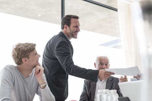Businessman handing over documents in conference room - ZEF007454