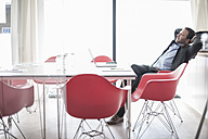 Businessman in conference room leaning back - ZEF007457