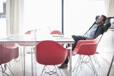 Businessman in conference room leaning back - ZEF007457