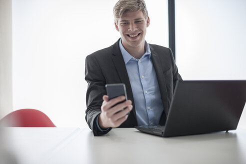 Smiling businessman at desk with cell phone and laptop - ZEF007124
