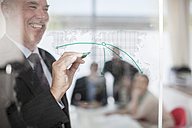 Businessman drawing on glass in meeting room - ZEF007108
