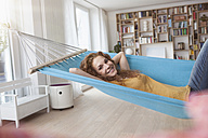 Smiling woman at home lying in hammock - RBF003054