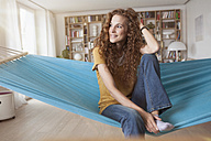 Smiling woman at home sitting in hammock - RBF003060