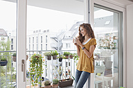 Smiling woman with cup of coffee leaning against balcony door - RBF003065