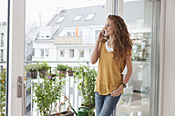 Smiling woman with leaning against balcony door on the phone - RBF003068