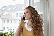 Smiling woman at home on the phone - RBF003070