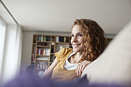 Smiling woman at home sitting on couch - RBF003073