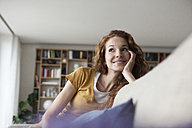 Smiling woman at home sitting on couch - RBF003074