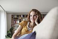 Smiling woman at home sitting on couch - RBF003075