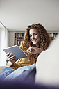 Smiling woman at home sitting on couch using digital tablet - RBF003076