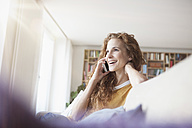 Smiling woman at home sitting on couch talking on cell phone - RBF003083